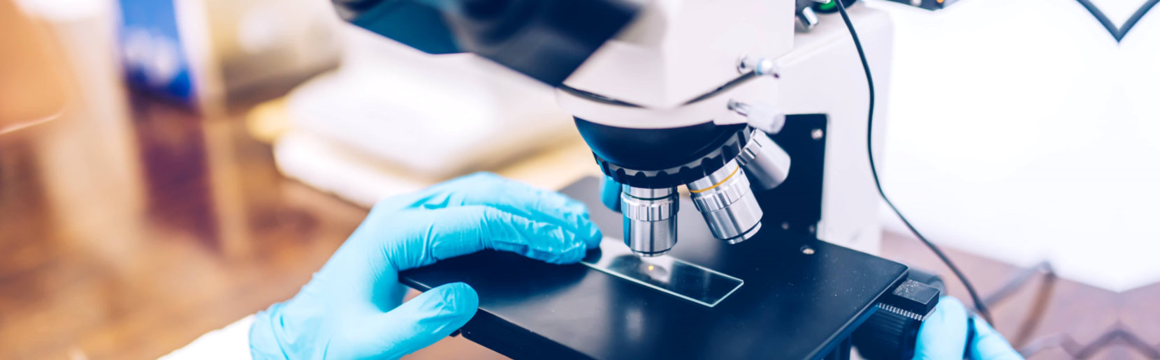 crop image of scientist using microscope